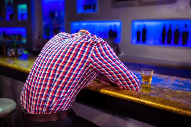 バーのカウンターの上に横たわる男の後姿