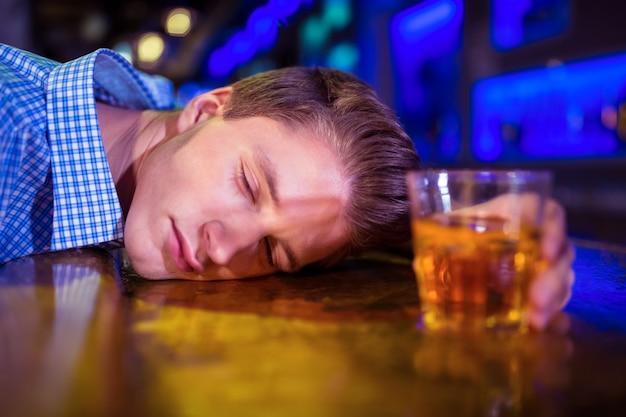 バーカウンターの上に横たわる酔っぱらい