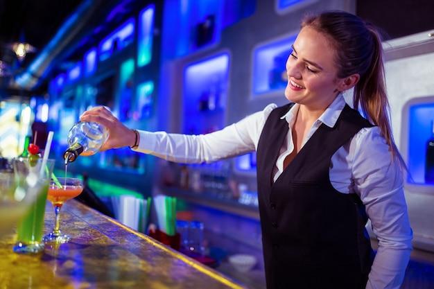 グラスに飲み物を注ぐ美しいバーテンダー