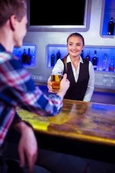 男にビールを提供する笑顔のバーテンダー