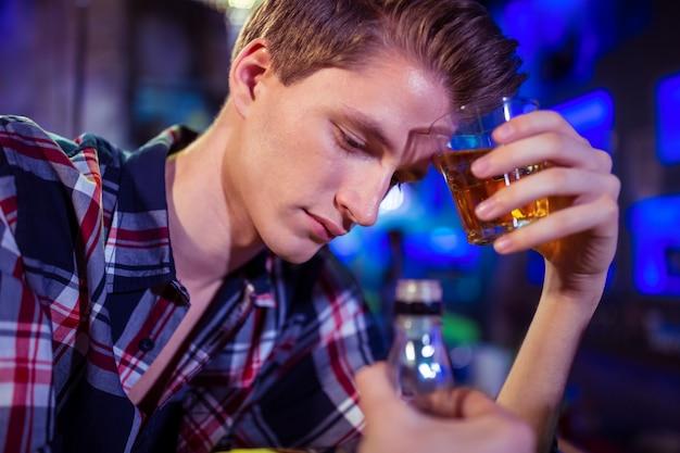 ウイスキーグラスを持って悲しい男