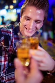 うれしそうな男と乾杯する友達のトリミング画像