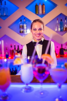 Молодая барменша стоит у освещенного прилавка