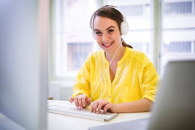 オフィスでキーボードで入力している間幸せなエグゼクティブの肖像画