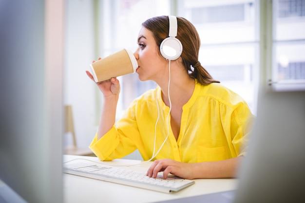 オフィスで入力しながらコーヒーを飲むエグゼクティブ