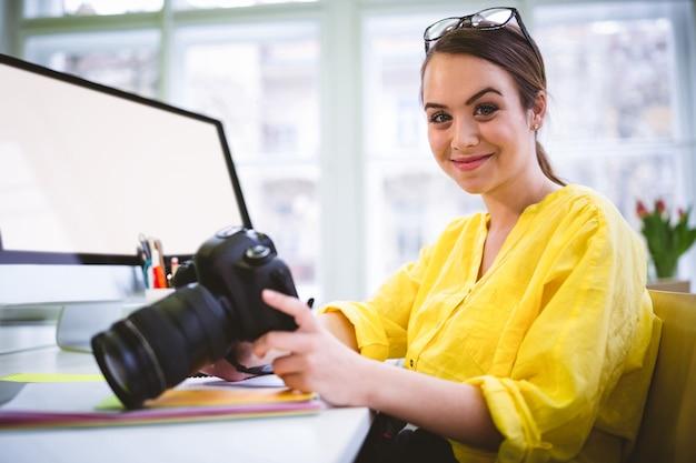 Портрет уверенно женского профессионала с камерой редактируя в офисе