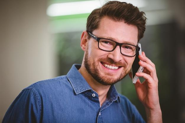 Портрет счастливого бизнесмена, говорить на мобильный телефон в офисе
