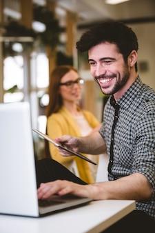 ラップトップを使用して女性の同僚と幸せなビジネスマン