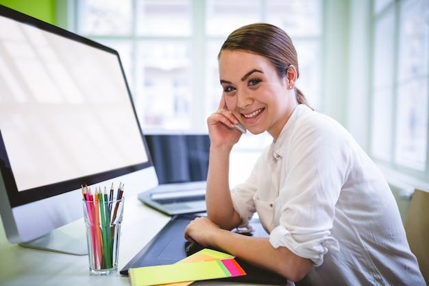 Женский графический дизайнер разговаривает по телефону на стол