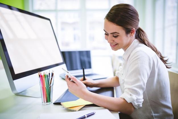 Графический дизайнер, глядя на телефон на столе