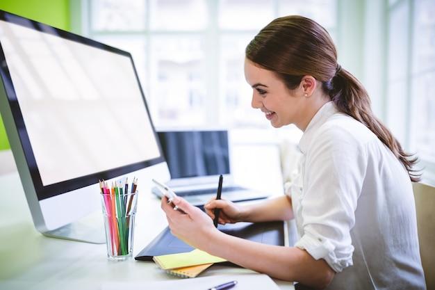 Графический дизайнер держит телефон во время работы