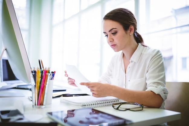 Серьезный женский графический дизайнер читает документ