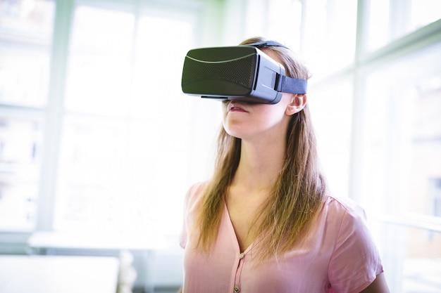 Графический дизайнер с использованием гарнитуры виртуальной реальности в офисе