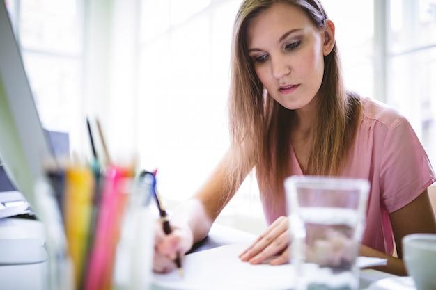 Графический дизайнер, написание документа на столе