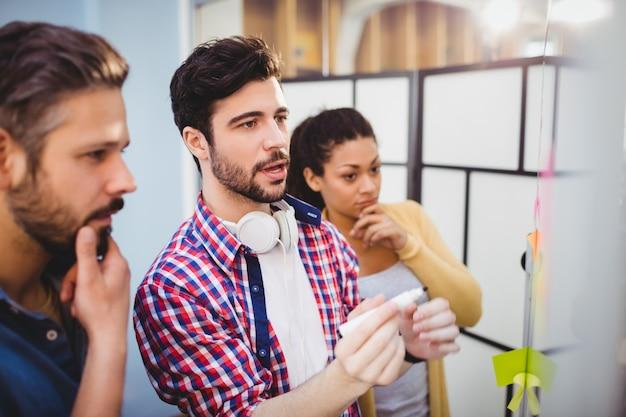Молодой исполнитель, объясняя стратегию в креативном офисе