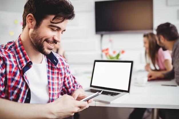 Счастливая исполнительная отправка смс на встрече в творческом офисе