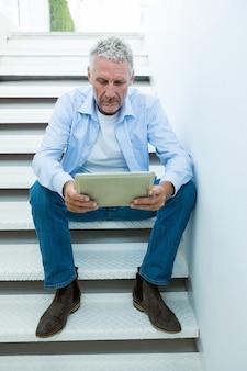 Зрелый человек держит планшет сидя на шагах