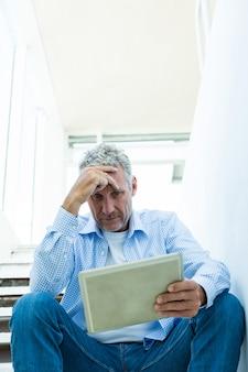 Потревоженный зрелый человек держа таблетку пока сидящ на шагах