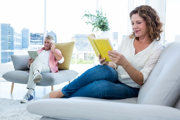 家で本を読んで笑顔の成熟した女性