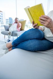 家で男と本を読んでいる女性の低いセクション