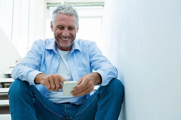 Счастливый зрелый человек с помощью смартфона на дому