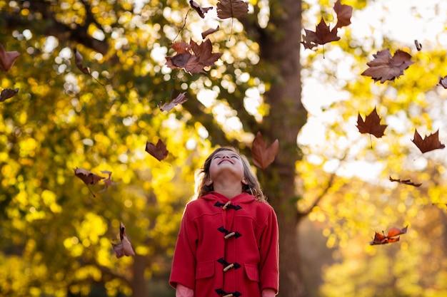 秋の秋の木に立っている幸せな女の子