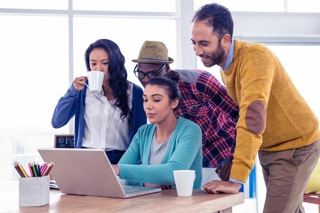 Деловые люди, использующие ноутбук на встрече в креативном офисе