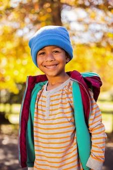秋の木に対して立っている幸せな少年