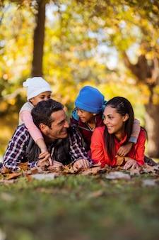 秋の間にフィールドに横たわっている陽気な家族