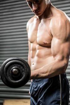 上半身裸の男がジムで重いダンベルを持ち上げる