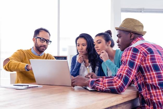 Серьезный бизнесмен обсуждает с коллегами на ноутбуке в креативном офисе