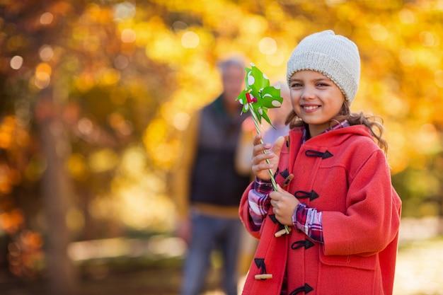 Веселая девушка с игрушкой вертушка в парке
