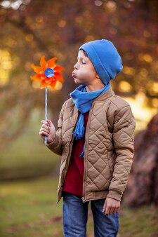 Мальчик дует вертушка в парке