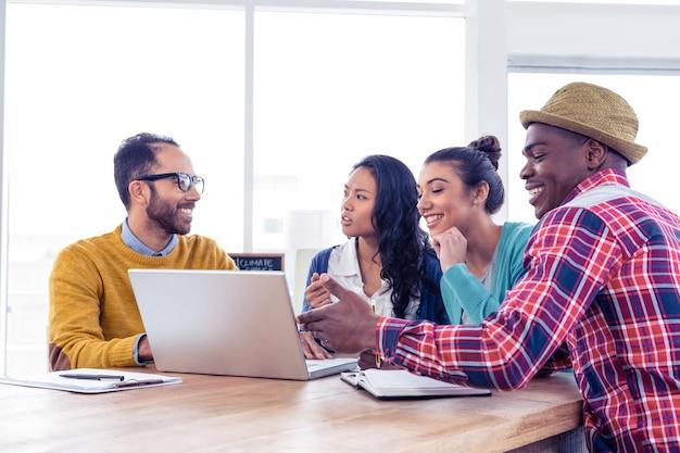 Молодые деловые люди обсуждают на ноутбуке в креативном офисе