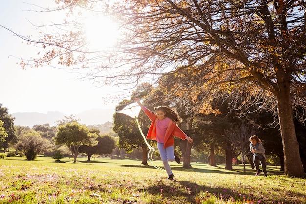 Девушка держит кайт во время бега в парке