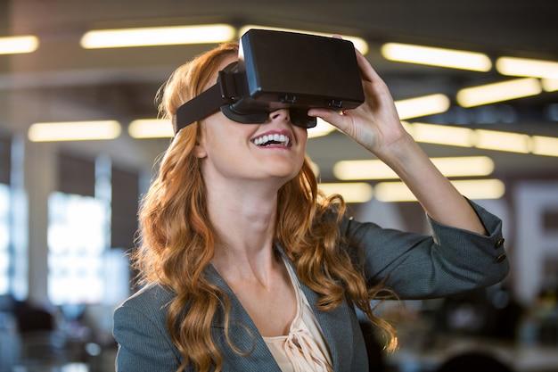Улыбается бизнесвумен, используя симулятор виртуальной реальности