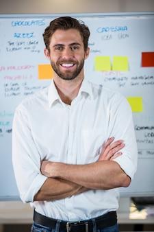Уверенный бизнесмен против доски в офисе