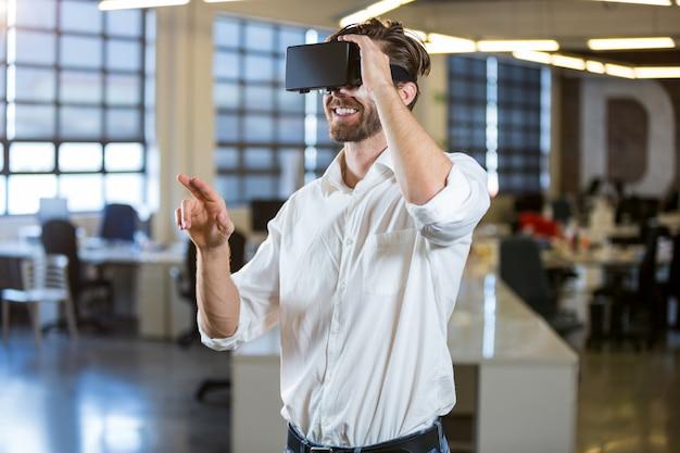 Бизнесмен, улыбаясь при использовании симулятора виртуальной реальности