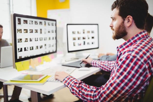 Редактор работает над фотографиями в креативном офисе