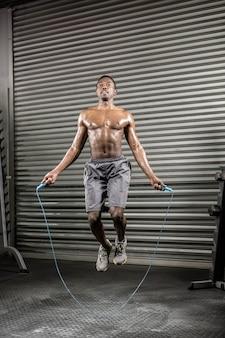 上半身裸の男がジムでロープをジャンプ