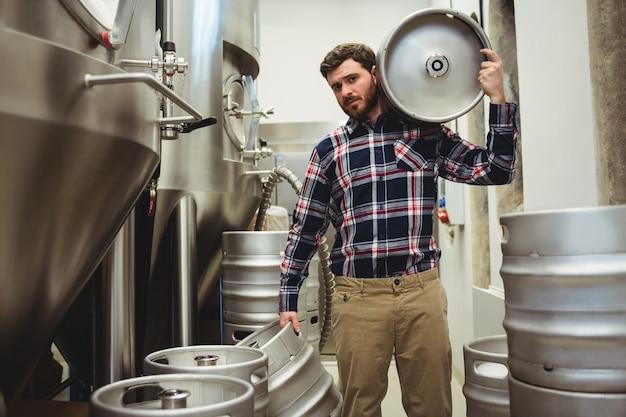 醸造所で樽を運ぶ若いメーカー