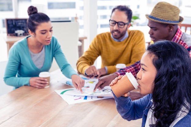 ビジネスの女性のクリエイティブオフィスで議論する同僚とコーヒーカップを飲む
