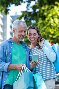 Улыбаясь пара с помощью мобильного телефона в городе