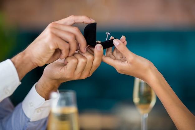 Мужчина предлагает женщине, предлагая обручальное кольцо