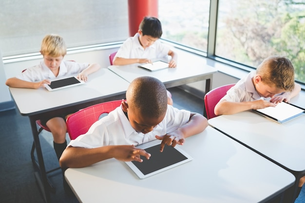 教室でデジタルタブレットを使用する子供たち
