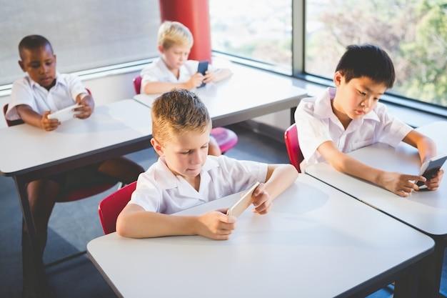 教室で携帯電話を使用する子供たち