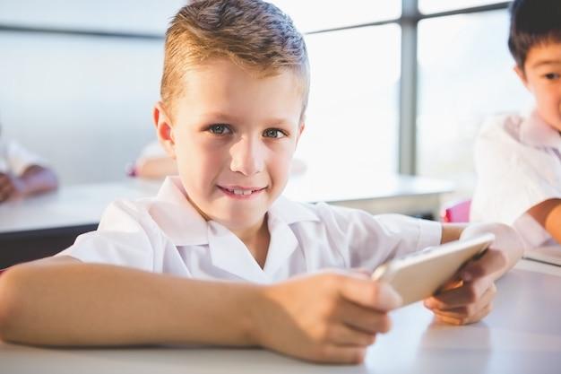 教室で携帯電話を使用して小学生