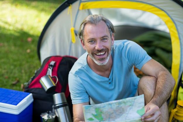 Портрет счастливого путешественника, держащего карту