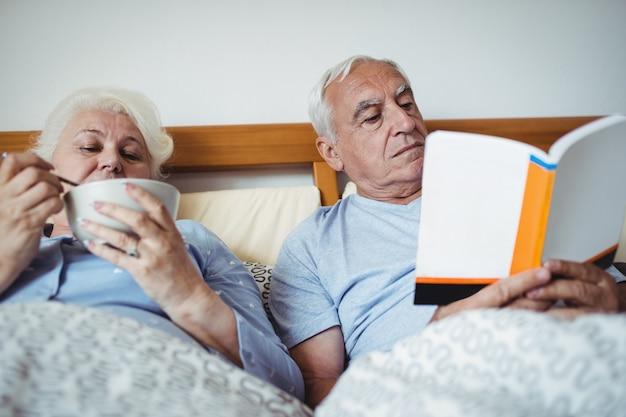 Пожилой мужчина читает роман и женщина завтракает