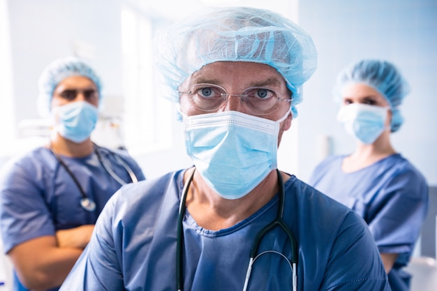 Хирург и медсестры, стоя в больнице
